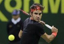 Federer of Switzerland returns ball to Zemlja of Slovakia during ATP Qatar Open tennis tournament in Doha